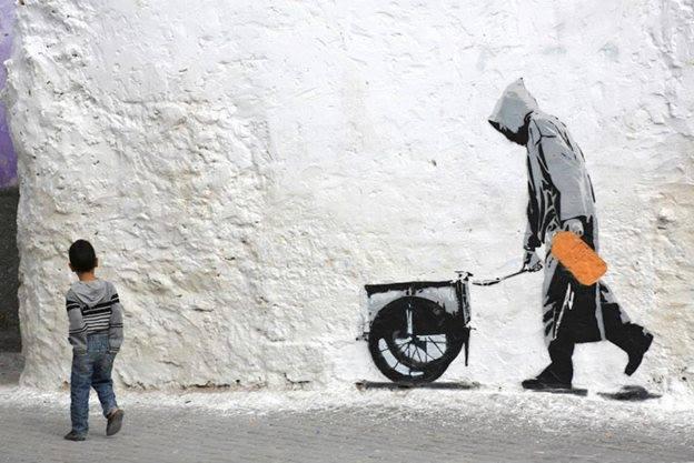 street art man pushing a charette + enfant dans la rue
